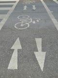 Segno della freccia e della bicicletta sul passaggio Immagini Stock
