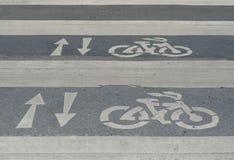 Segno della freccia e della bicicletta sul passaggio Fotografia Stock