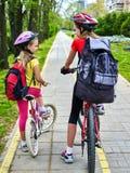 Segno della pista ciclabile con i bambini Ragazze che indossano casco con lo Zaino Fotografie Stock
