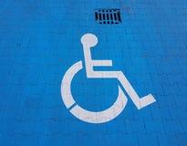 Segno della segnaletica stradale su un fondo blu che denota parcheggio per un veicolo disabile La convenienza di parcheggio del v fotografia stock libera da diritti