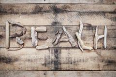 Segno della spiaggia fatto di legname galleggiante su un fondo di legno fotografie stock libere da diritti