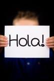 Segno della tenuta del bambino con la parola spagnola Hola - ciao fotografie stock