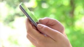 Segno dello scorrevole della giovane donna sul telefono cellulare dello schermo attivabile al tatto nel parco archivi video