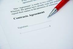 Segno di accordo di contratti sulla carta del documento con la penna rossa Immagine Stock Libera da Diritti