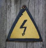 Segno di alta tensione del ferro Inchiodato ad un giallo di legno della posta closeup Fotografia Stock Libera da Diritti