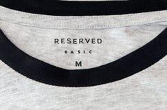 Segno di base riservato con informazioni sulla dimensione sulla maglietta Riservato è un segno polacco del panno fotografia stock