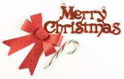 Segno di Buon Natale con l'arco ed il bastoncino di zucchero rossi Fotografie Stock Libere da Diritti