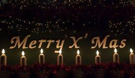 Segno di Buon Natale con la candela e l'indicatore luminoso fotografie stock libere da diritti