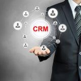 Segno di CRM (customer relationship management) indicato da un uomo d'affari Immagine Stock