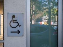 Segno di handicap sulla parete all'aperto che indica destra fotografia stock