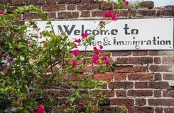 Segno di immigrazione su un vecchio muro di mattoni Fotografia Stock