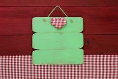 Segno di legno in bianco del menu dalla tovaglia rossa del percalle che appende sul fondo di legno Fotografie Stock Libere da Diritti