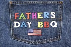 Segno di legno del BBQ di giorno di padri sulla tasca delle blue jeans fotografie stock
