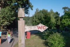 Segno di legno della freccia alla toilette unisex o toilette nel parco della città Immagini Stock Libere da Diritti
