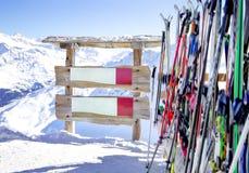 Segno di legno per testo vicino allo sci ed al palo di sci e le montagne del wint delle attrezzature dello sci su un fondo Immagini Stock