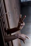 Segno di pace da una cella di prigione immagini stock