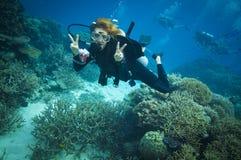 Segno di pace infiammante dell'operatore subacqueo la grande barriera Fotografia Stock