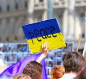 Segno di pace sulla bandiera ucraina nella manifestazione di protesta contro la guerra fotografia stock