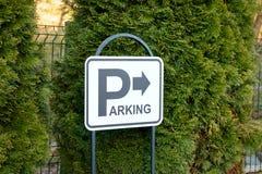 Segno di parcheggio con una freccia alla destra su un fondo del tuja Fotografia Stock
