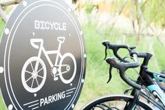Segno di parcheggio della bicicletta con gli ambiti di provenienza dell'erba verde Immagini Stock Libere da Diritti