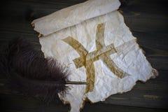Segno di pesci dello zodiaco su carta d'annata con la vecchia penna sullo scrittorio di legno Fotografia Stock