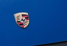 Segno di Porsche sul cappuccio blu dell'automobile Fotografia Stock