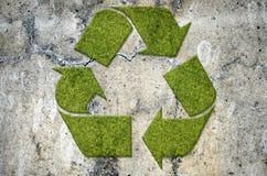 Segno di riciclaggio verde su un muro di cemento Fotografie Stock Libere da Diritti
