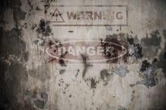 Segno di rischio sbiadito sulla parete incrinata del cemento Fotografia Stock