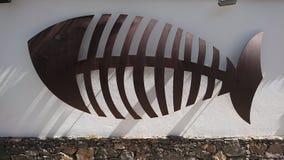 Segno di scheletro del pesce sulla parete bianca Fotografia Stock