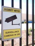 Segno di sorveglianza della macchina fotografica su un recinto d'acciaio di una zona industriale Immagini Stock