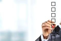 Segno di spunta del giovane uomo d'affari sulla lista di controllo con l'indicatore Immagine Stock