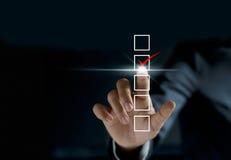 Segno di spunta dell'uomo d'affari sulla lista di controllo con un indicatore rosso Fotografia Stock