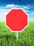 Segno di tema di arresto rosso disposto in un campo di erba con stanza per lo spazio della copia o del testo Immagini Stock
