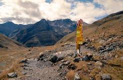 Segno di trekking sul prato alpino dell'erba circondato dalle alte montagne in alpi svizzere Immagine Stock