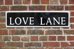 Segno di via per il vicolo di amore sul muro di mattoni Immagine Stock