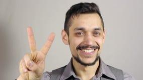 Segno di Victory By Businessman con una barba su fondo grigio archivi video