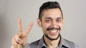 Segno di Victory By Businessman con una barba su fondo grigio stock footage