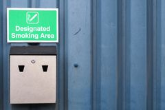 Segno di zona fumatori e vassoio di cenere designati del metallo alla parete di affari del lavoro fotografia stock