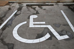 Segno disabile del permesso di parcheggio dipinto su parcheggio dell'automobile Immagine Stock
