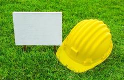 Segno e casco di sicurezza di legno bianchi Fotografie Stock