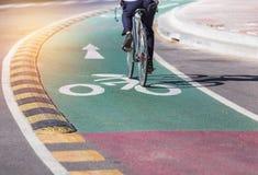 segno e freccia bianchi della pista ciclabile sulla strada asfaltata verde Fotografie Stock Libere da Diritti
