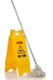 Segno e mop bagnati del pavimento su priorità bassa bianca immagini stock