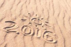 Segno 2016 e sole scritto sulla spiaggia sabbiosa Concetto di viaggio di estate Fotografie Stock Libere da Diritti