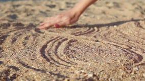 Segno femminile di infinito del disegno della mano sulla sabbia stock footage