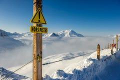 Segno fuori-pista alle montagne in nuvole con neve nell'inverno Fotografia Stock