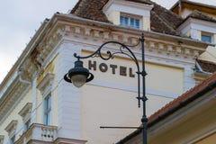 Segno generico dell'hotel incorniciato da una lampada di via artisticamente curva, con le vecchie costruzioni rinnovate nei prece fotografia stock