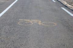 Segno giallo della bicicletta su asfalto Fotografia Stock Libera da Diritti