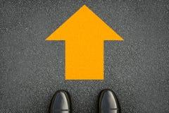 Segno giallo della freccia sulla via Fotografie Stock