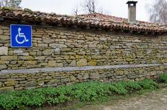 Segno invalido di parcheggio sulla vecchia parete di pietra Immagini Stock