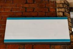 Segno metallico bianco su un muro di mattoni Fotografia Stock